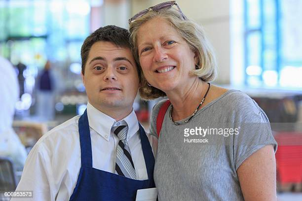 Portrait of a man with Down Syndrome working at a grocery store and greeting a customer