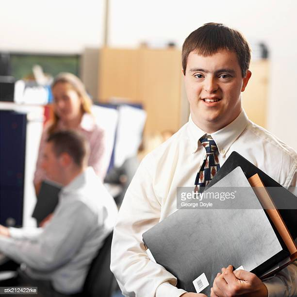 portrait of a man with down syndrome working in an office - down syndrome stock pictures, royalty-free photos & images