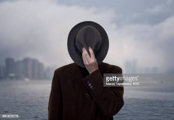 portrait of a man with face covered by the hat. - raadsel stockfoto's en -beelden