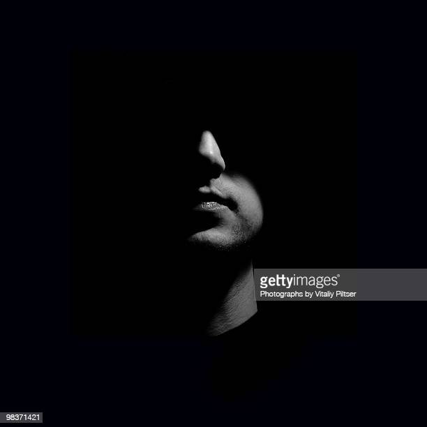 portrait of a man with face half lit. - nicht erkennbare person stock-fotos und bilder