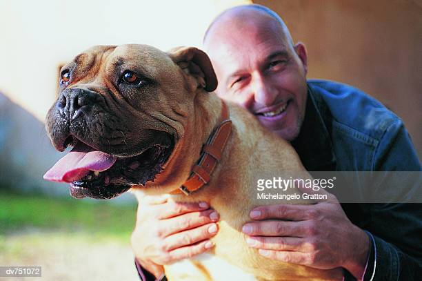 portrait of a man with his arms around a staffordshire bull terrier - pit bull terrier fotografías e imágenes de stock