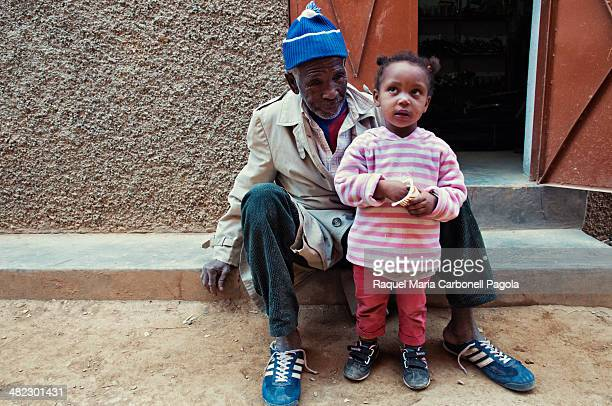 Portrait of a man with his with little girl sitting at a house doorway in an small village