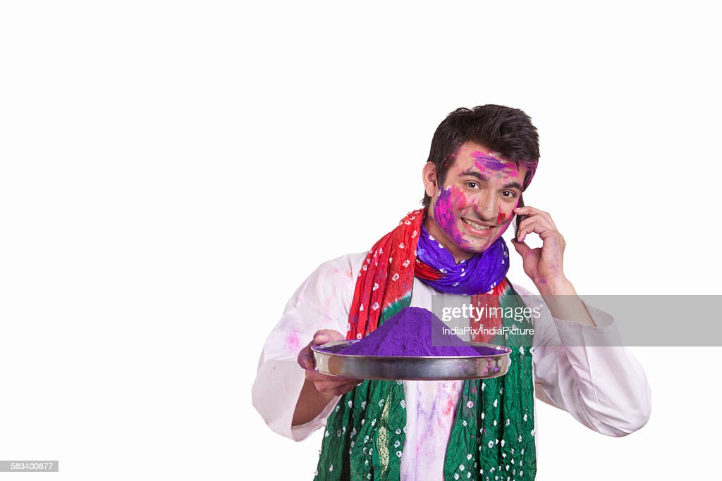 Portrait of a man with holi colour talking on a mobile phone : Stock Photo