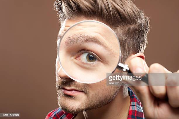 portrait of a man with magnifying glass - magnifying glass stock pictures, royalty-free photos & images
