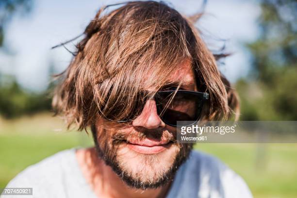 Portrait of a man with unkempt hair wearing sunglasses