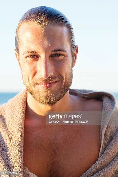 portrait of a man wrapped in a towel and smiling - onoky stock-fotos und bilder