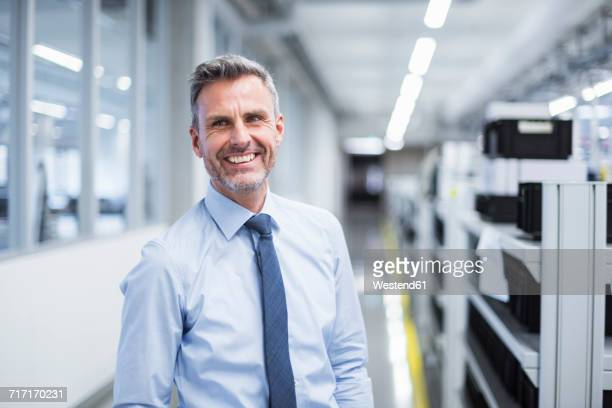 portrait of a manager on the shop floor of a factory - overhemd en stropdas stockfoto's en -beelden