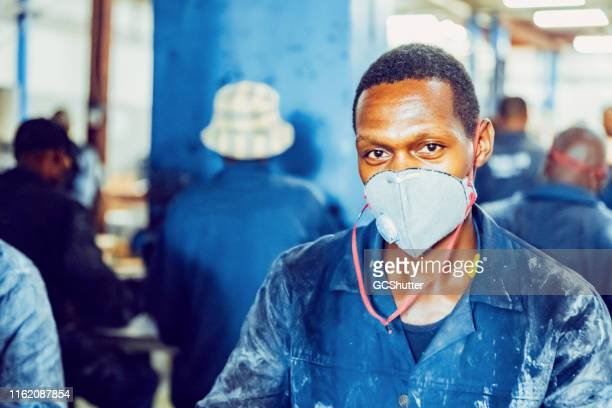 portrait of a manual african workers working at a factory in africa - may day stock pictures, royalty-free photos & images