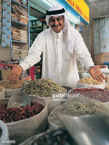Portrait of a Market Trader Wearing Traditional Middle Eastern Dress and Showing His Wares in a Souk, Dubai