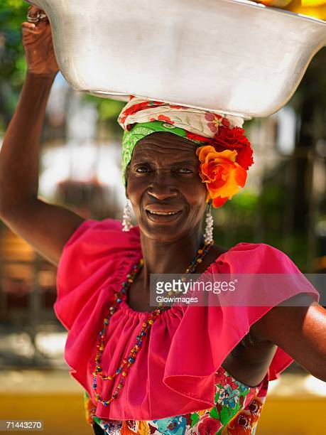 portrait of a market vendor carrying a basket on her head, cartagena, colombia - cartagena colombia foto e immagini stock