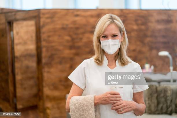 portrait of a masseuse working at a spa and wearing a facemask - body care stock pictures, royalty-free photos & images