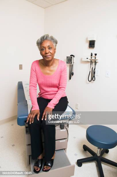 portrait of a mature adult female patient sitting on an examination table - hand on knee stock pictures, royalty-free photos & images