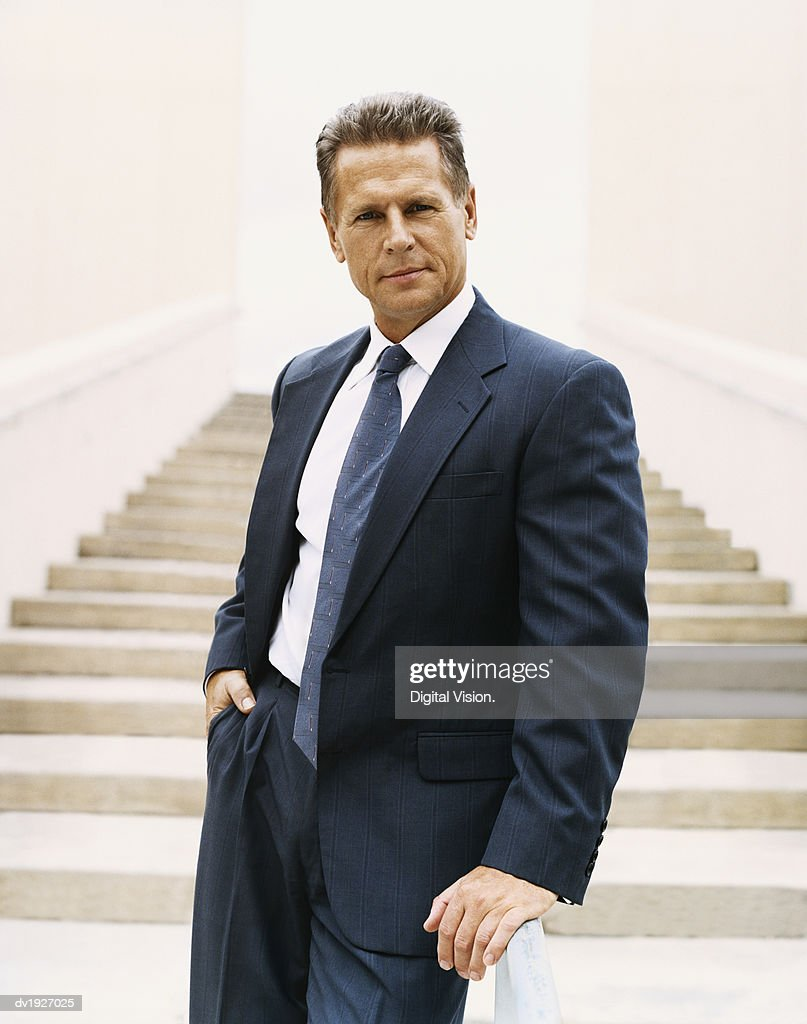 Portrait of a Mature Businessman Standing at the Bottom of Steps : Stock Photo