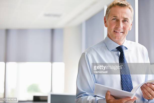 Portrait of a mature businessman with document at office, smiling