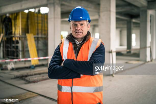 portrait of a mature caucasian construction site foreman - work helmet stock pictures, royalty-free photos & images