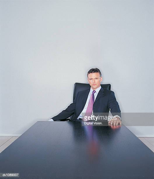 Portrait of a Mature CEO Sitting at the End of a Long Table