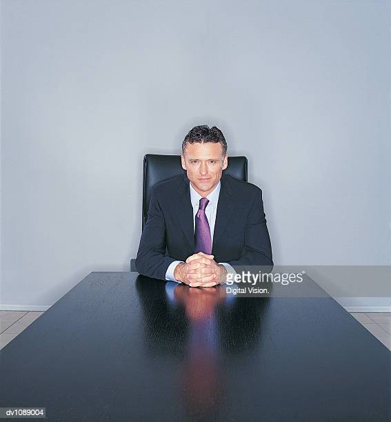Portrait of a Mature CEO Sitting at the End of a Long Table With His Hands Clasped Together