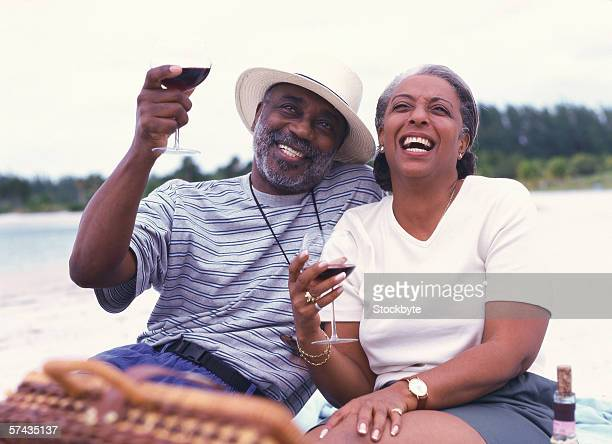 portrait of a mature couple enjoying red wine on the beach