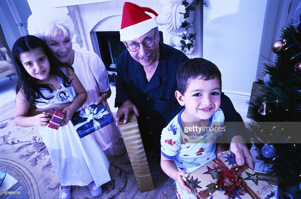 Portrait Of A Mature Couple Giving Their Grandchildren Christmas ...