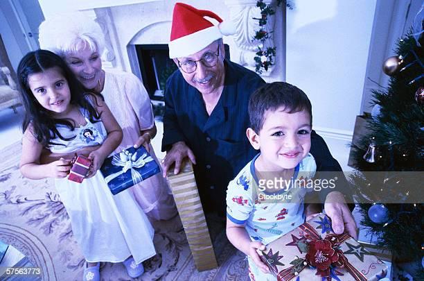 portrait of a mature couple giving their grandchildren Christmas presents