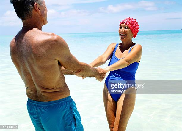portrait of a mature couple holding hands at the beach