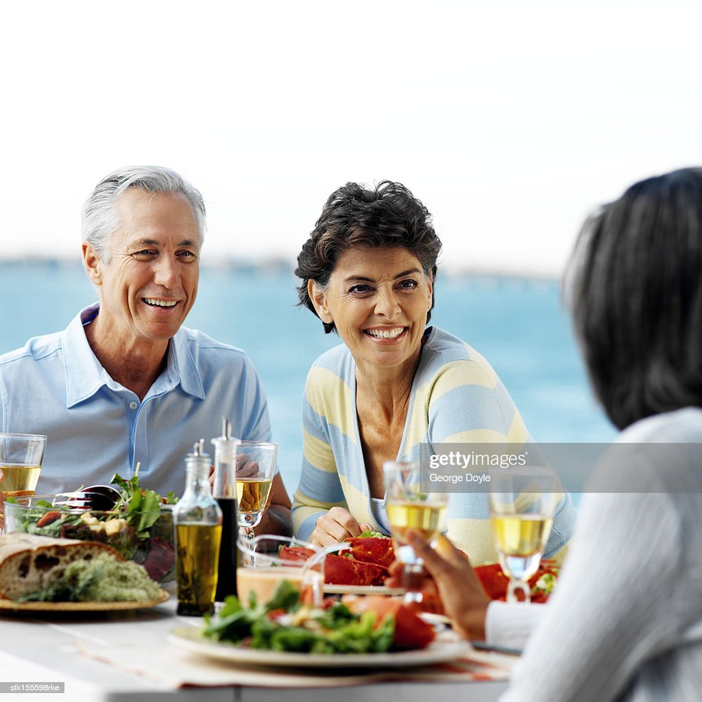 portrait of a mature couple sitting at an outdoor dining table stock