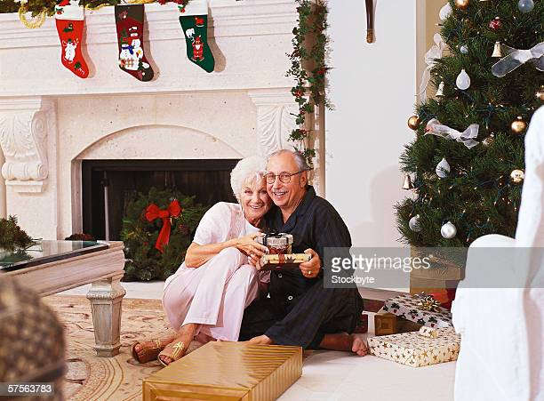 portrait of a mature couple sitting besides a christmas tree with presents - stockings no shoes stock pictures, royalty-free photos & images