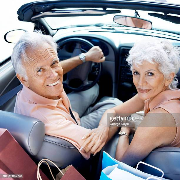 portrait of a mature couple sitting in a convertible car