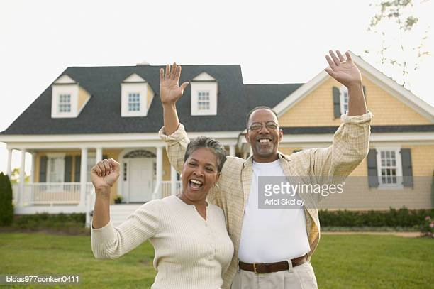 portrait of a mature couple standing together with their arms raised in front of a house - fully unbuttoned stock pictures, royalty-free photos & images