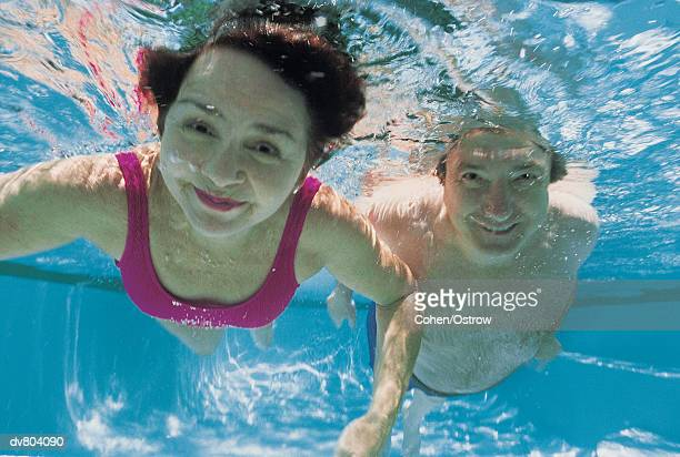 portrait of a mature couple swimming underwater - casal heterossexual imagens e fotografias de stock