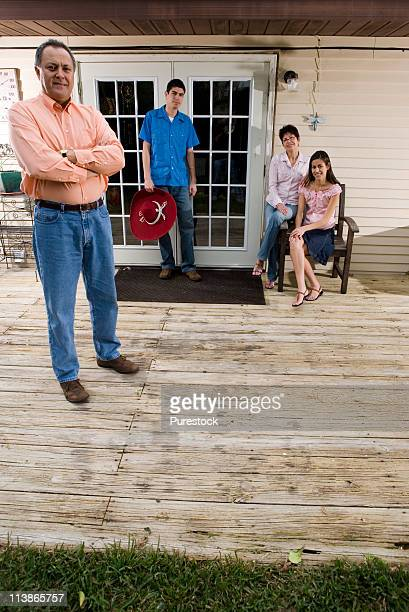 Portrait of a mature couple with their adult children at the doorway of their house