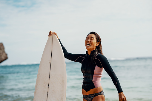 Portrait of a mature female athlete with her surfboard with a confident expression - gettyimageskorea