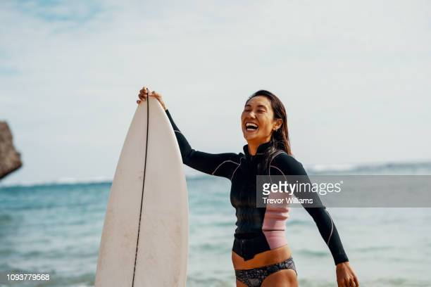 portrait of a mature female athlete with her surfboard with a confident expression - leisure activity stock pictures, royalty-free photos & images