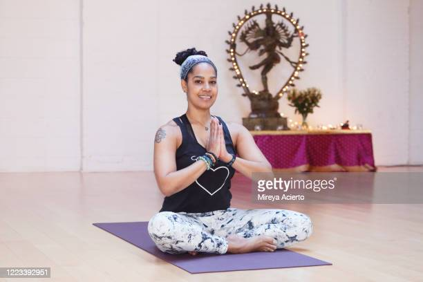 Portrait of a mature LatinX woman with curly hair, smiling with hands in prayer position, with a Hindu god sculpture in the background of a yoga studio.