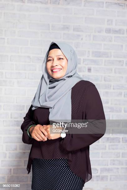 portrait of a mature malaysian woman - malay hijab stock photos and pictures