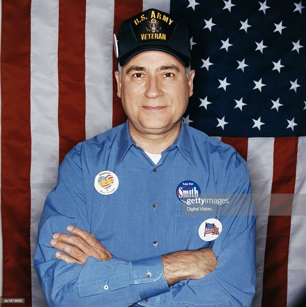 Portrait of a Mature Male Veteran Standing in Front of a Stars and Stripes Flag Wearing Election Badges : Stock Photo