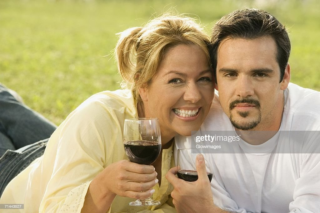 Portrait of a mature man and a young woman holding glasses of red wine : Stock Photo