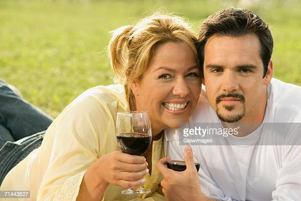 portrait of a mature man and a young woman holding glasses of red wine - cougar woman fotografías e imágenes de stock