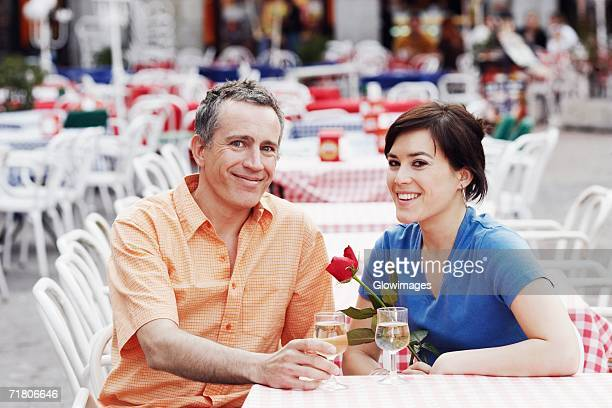 Portrait of a mature man and a young woman sitting together at a sidewalk cafe