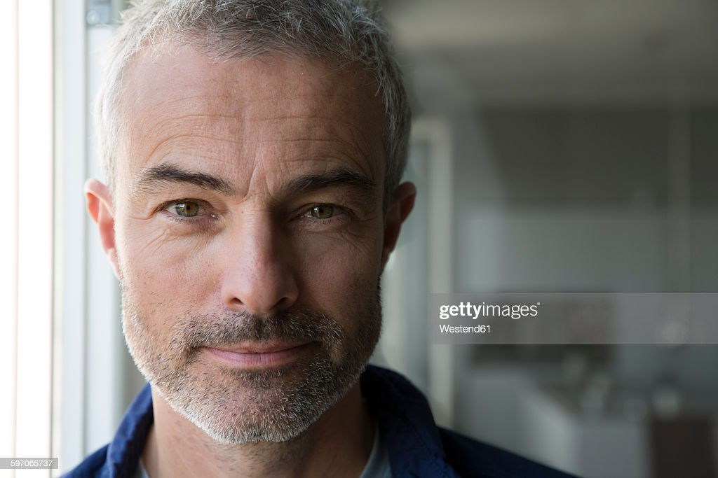 Portrait of a mature man at the window : Stock Photo