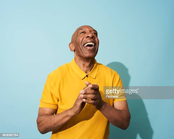 portrait of a mature man dancing, smiling and having fun - colored background stock pictures, royalty-free photos & images