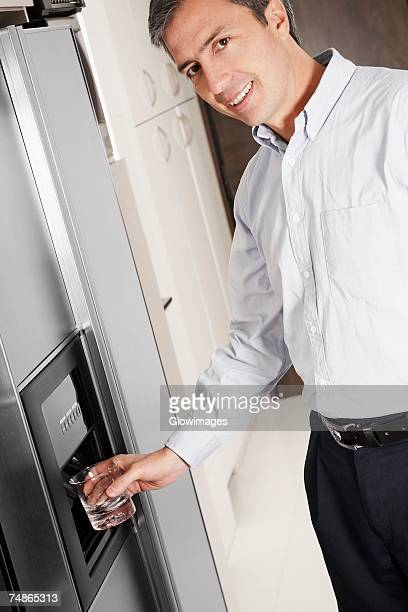 Portrait of a mature man filling water in a glass from a refrigerator dispenser