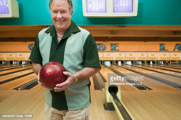 Portrait of a mature man holding a bowling ball in a bowling alley