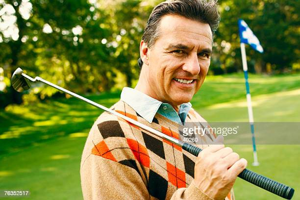 portrait of a mature man holding a golf club - golf lustig stock-fotos und bilder