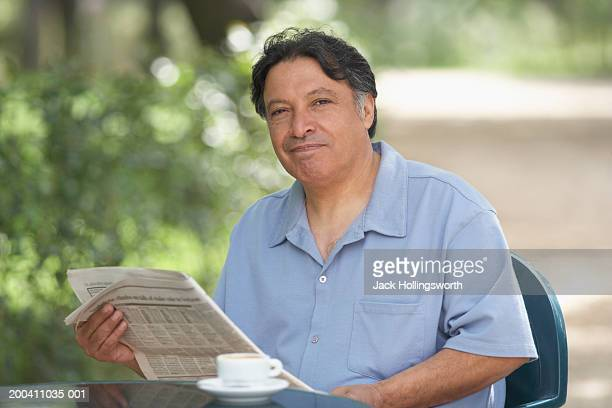 Portrait of a mature man holding a newspaper