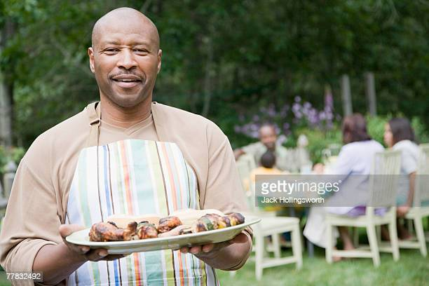 Portrait of a mature man holding a plate of food
