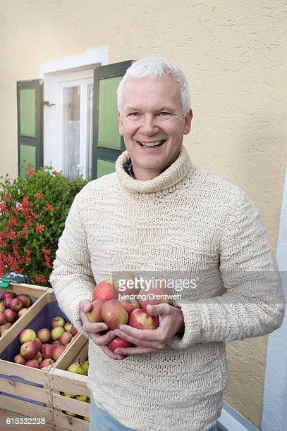 Portrait of a mature man holding apples in his hands in front of wholefood shop and smiling, Bavaria, Germany