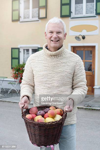 Portrait of a mature man holding basket full of apples in his hands in front of wholefood shop and smiling, Bavaria, Germany