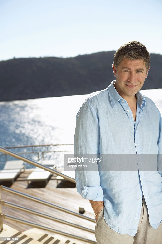 Portrait of a Mature Man in a Summer Shirt, Standing on Steps by the Water : Stock Photo