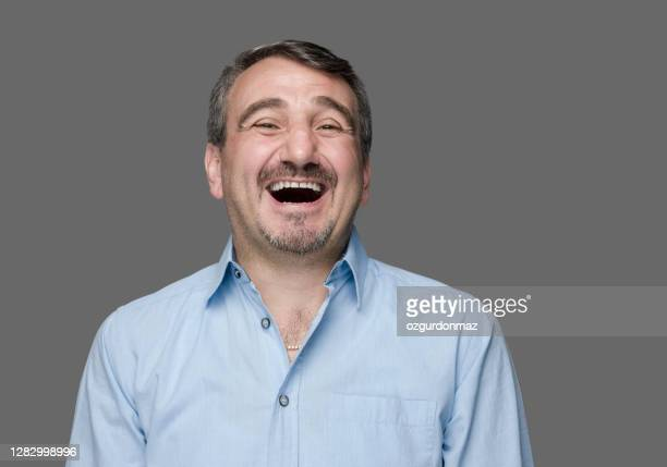 portrait of a mature man laughing, gray background, studio shot - one mature man only stock pictures, royalty-free photos & images